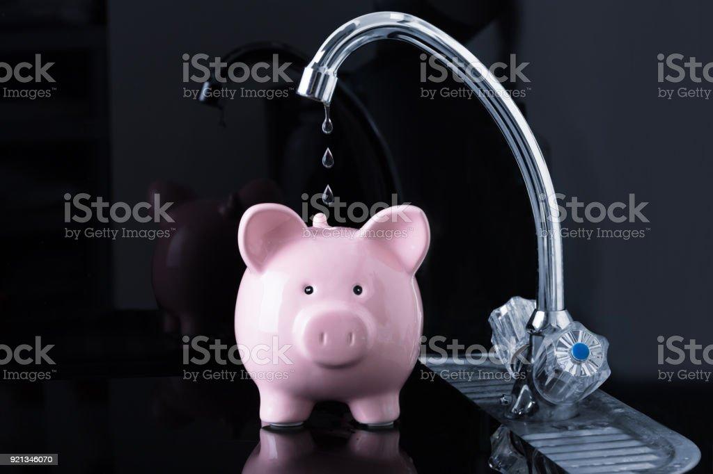 Cae gota de agua de goteo del grifo dentro la Piggybank - foto de stock
