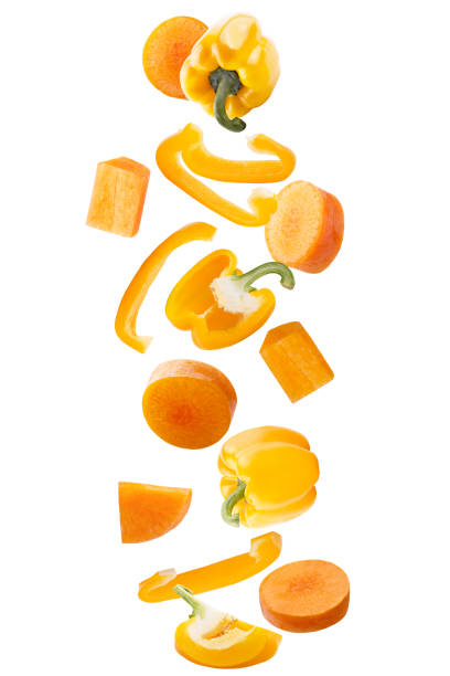Falling fresh yellow sweet pepper and carrots isolated on white background with clipping path as package design element and advertising. stock photo