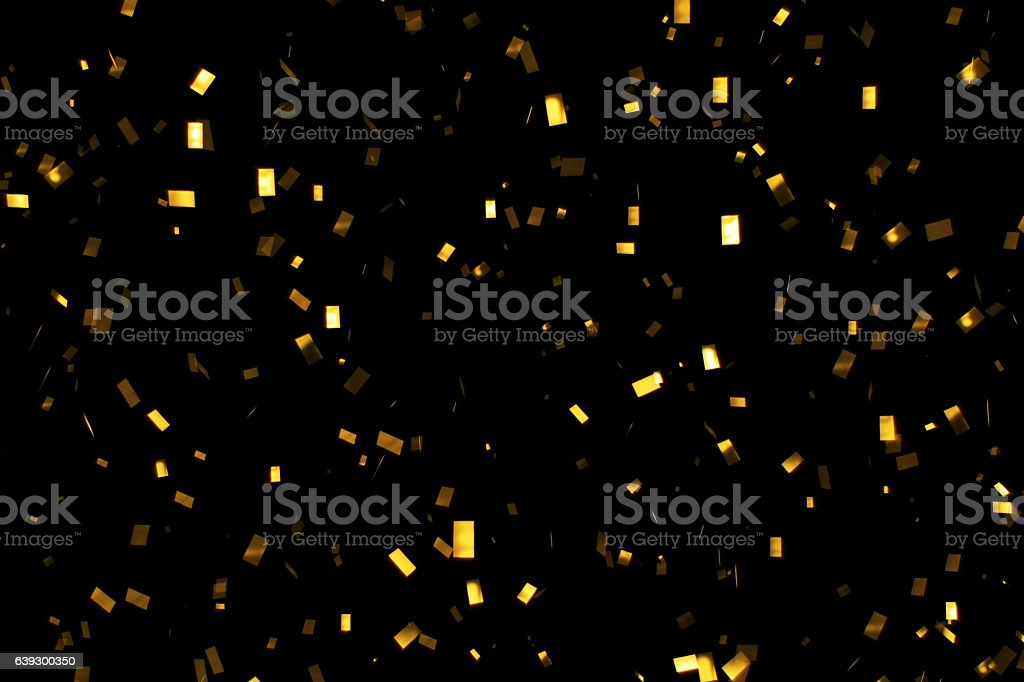 falling gold glitter foil confetti,  on black background stock photo