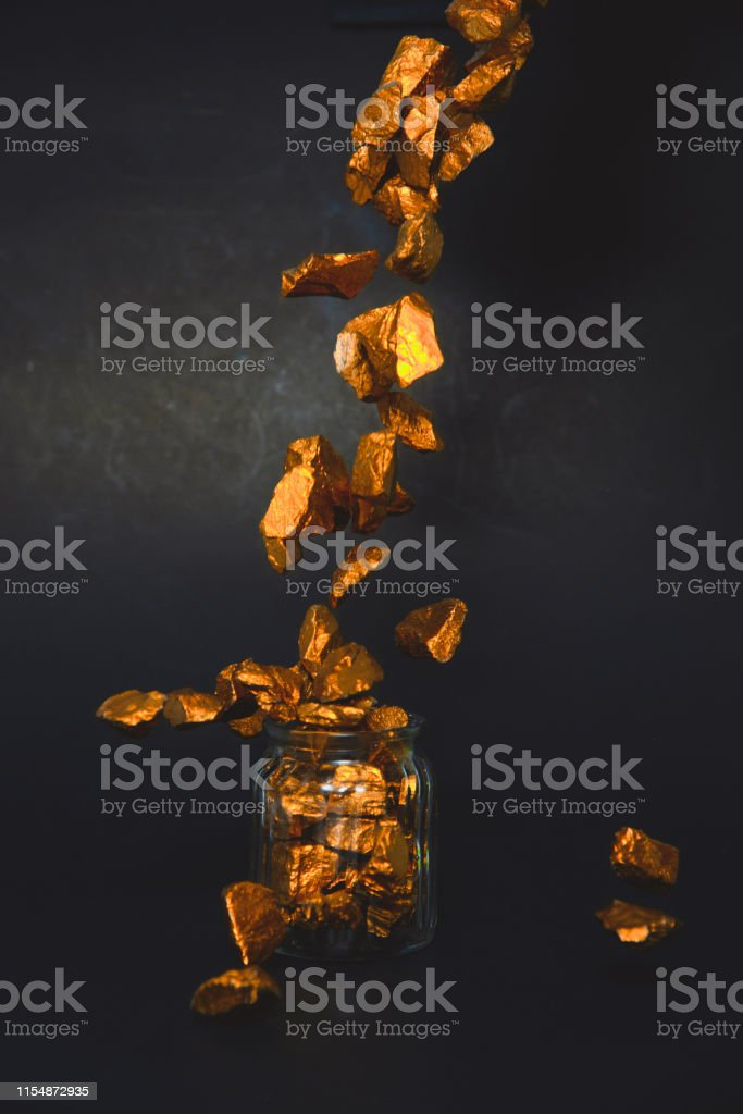 Falling Gold Nuggets Or Gold Ore And Glass Jar In Dark Room