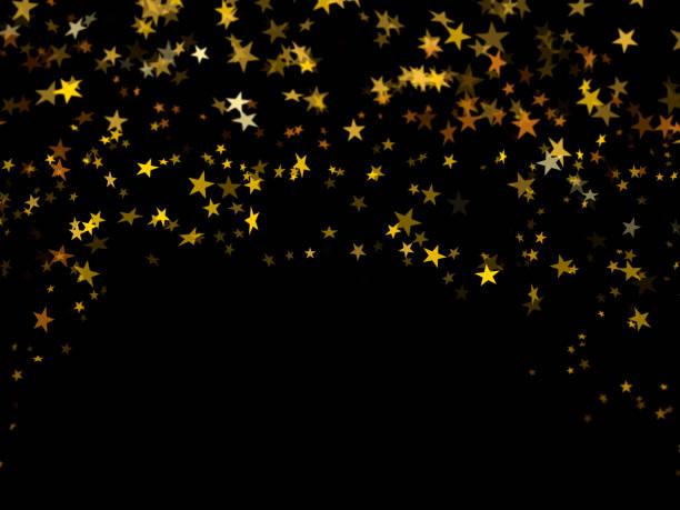 Falling golden confetti stars on black background stock photo