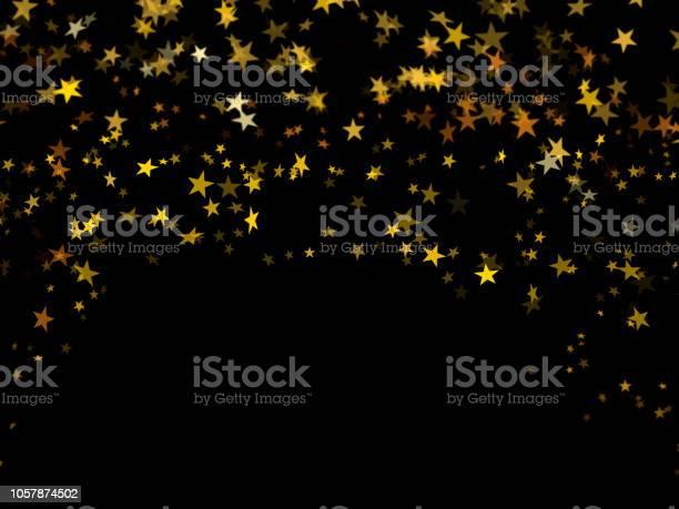 Photo of Falling golden confetti stars on black background