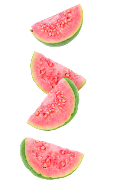 Falling guava slices Isolated guava slices. Four wedges of green pink fleshed guava fruits isolated on white background with clipping path guava stock pictures, royalty-free photos & images