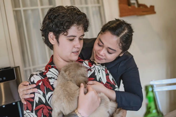 Falling in love with this new puppy Shot of interracial lesbian couple playing with their puppy at home. An androgynous female sitting while hugging a puppy and her girlfriend hugging from behind. cisgender stock pictures, royalty-free photos & images
