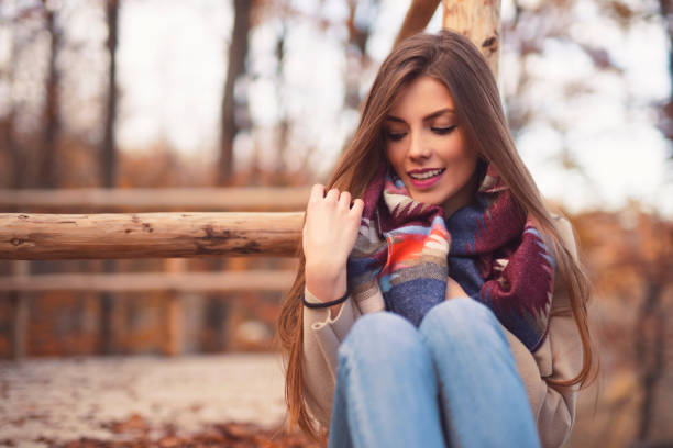 Falling Into A Daydream Portrait of a beautiful young woman sitting outdoors and daydreaming. straight hair stock pictures, royalty-free photos & images