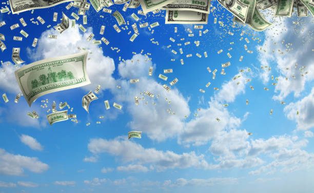 falling large group of money of American dollar bills over sky stock photo
