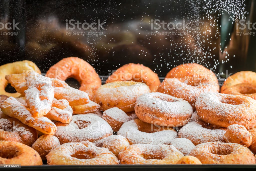 Falling powdered sugar on fresh homemade donuts stock photo
