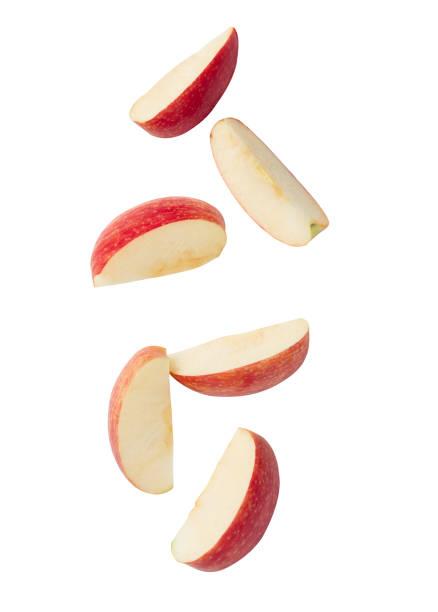 fatia de maçã vermelha caindo isolada em fundo branco com caminho de recorte - fatia - fotografias e filmes do acervo