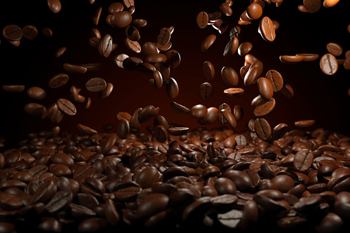 Falling roasted coffee beans on brown background