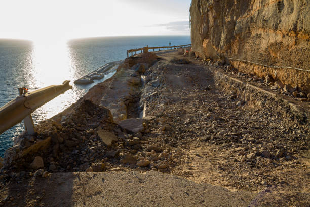 Falling rocks and big collapse hole on closed mountain road under the sea. stock photo