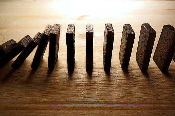 Falling row of dominoes on wooden surfaces stock photo