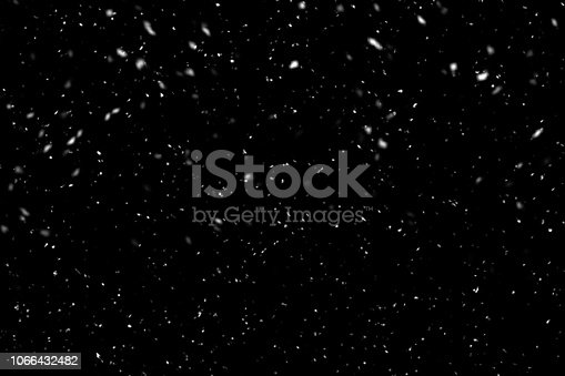 Falling snow on black background. Winter background in pure dark. Heavy snow.