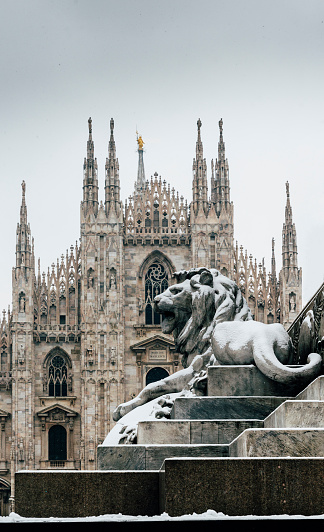 Falling snowflakes at ornate of lion on Piazza del Duomo in Milan, Lombardy, Italy. The Patron Saint of Milan, Madonnina, is visible above the Duomo Cathedral, with copy space