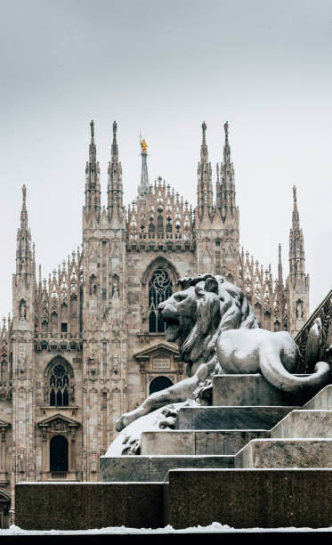 Falling snowflakes at ornate of lion on Piazza del Duomo in Milan, Lombardy, Italy. The Patron Saint of Milan, Madonnina, is visible above the Duomo Cathedral, with copy space stock photo