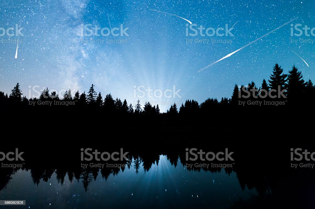 Falling stars Lake pine trees silhouette Milky Way stock photo