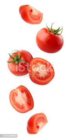 falling tomatoes isolated on a white background with a clipping path. whole red tomatoes and cut pieces fly in the air. vegetables fall down.