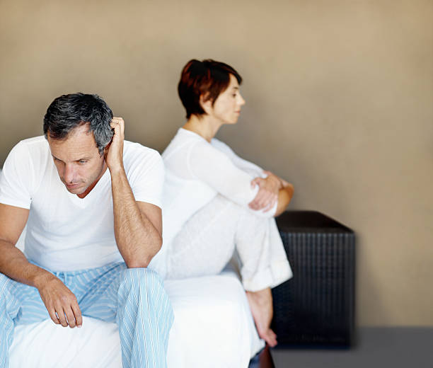 Fallout after a disagreement A depressed couple sitting apart from one another after a disagreement erectile dysfunction stock pictures, royalty-free photos & images