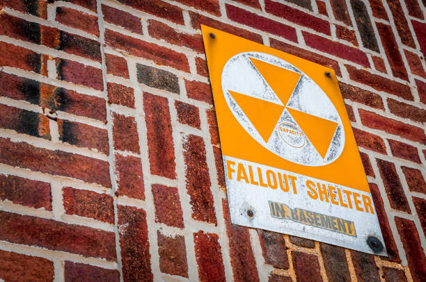 fallout shelter zone sign on red brick with copyspace A cold war era fallout shelter zone sign on old red brick building indicating specific buildings as refuge in case of a nuclear or biological attack over the United States with copy space bomb shelter stock pictures, royalty-free photos & images