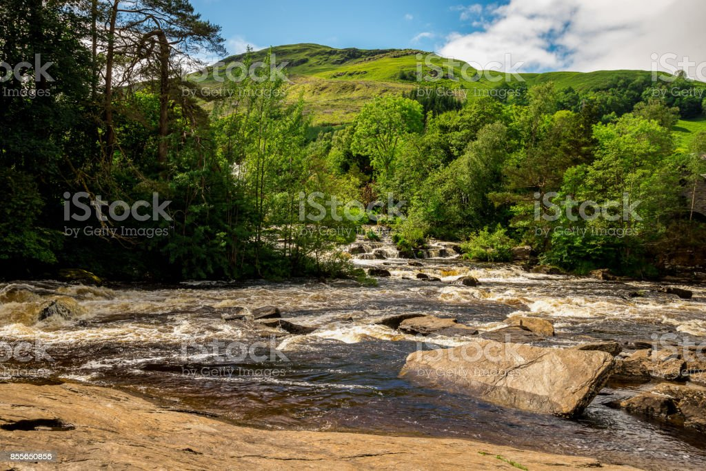 Falls of Dochart and mountain background landscape at town of Killin, central Scotland stock photo