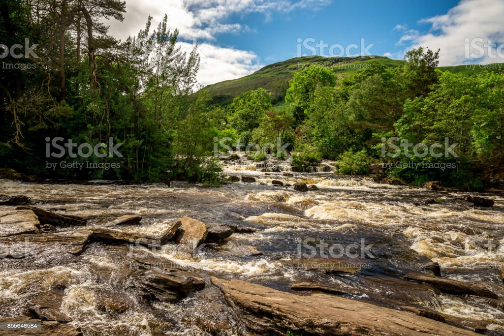 Falls of Dochart river and mountain background landscape at town of Killin, central Scotland stock photo