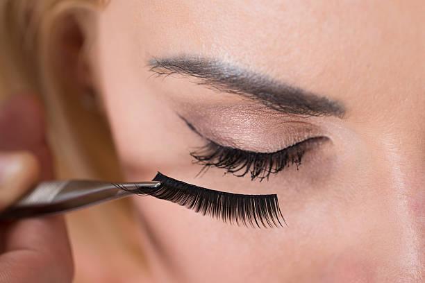 False Eyelashes Being Put On Woman's Eye Close-up of false eyelashes being put on woman's eye false eyelash stock pictures, royalty-free photos & images