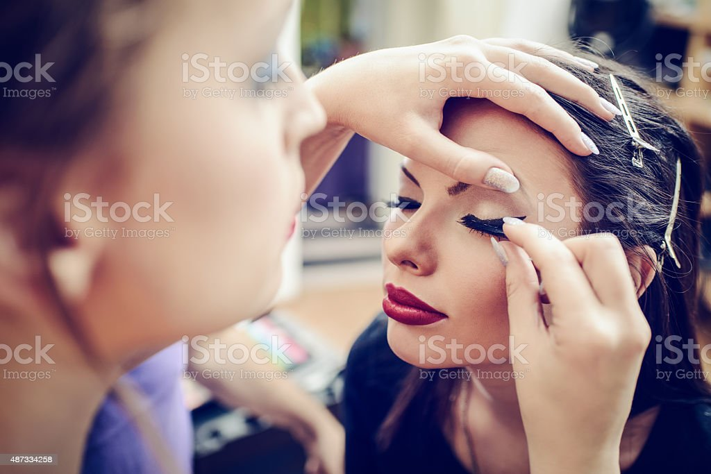 False Eyelashes Make-up artist applying the false eyelashes to model. Close up. 2015 Stock Photo