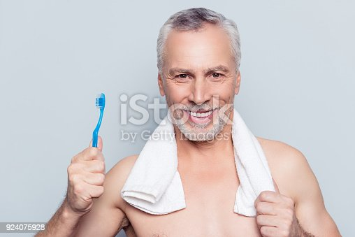 istock False fake teeth care concept. Close up portrait of cheerful excited glad pleased with shiny beaming toothy smile grandpa using blue toothbrush towel on shoulders isolated on gray background 924075928