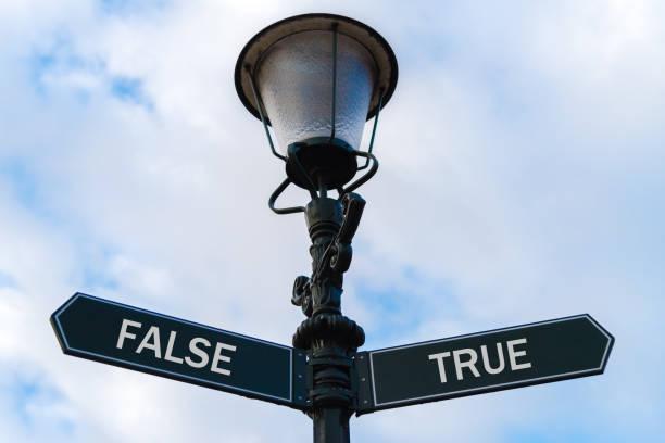 false versus true directional signs on guidepost - wahre lügen stock-fotos und bilder