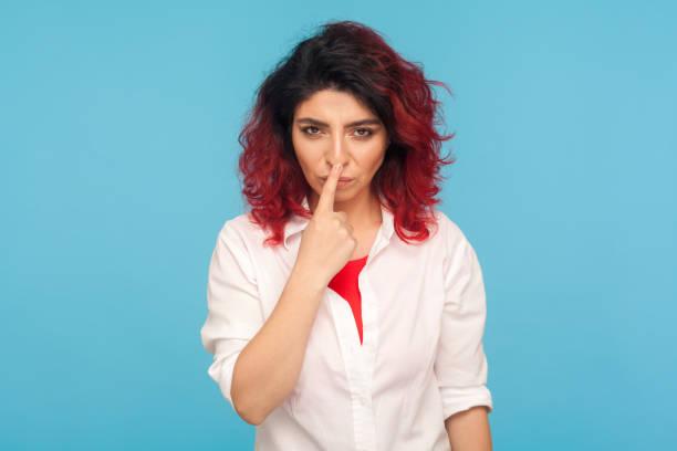 falschheit zeichen. porträt von wütend unzufriedene frau mit ausgefallenen roten haaren in weißem hemd berühren nase mit lüge geste - pig ugly stock-fotos und bilder