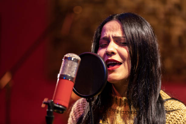 Famele singer performing for recording in sound studio stock photo