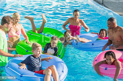 1091098220 istock photo Families and friends at water park on lazy river 912785918