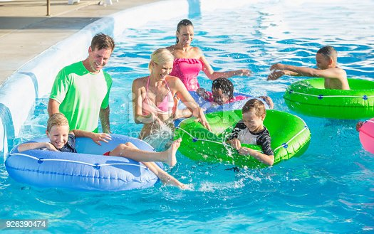 1091098220 istock photo Families and friends at water park on lazy river 926390474