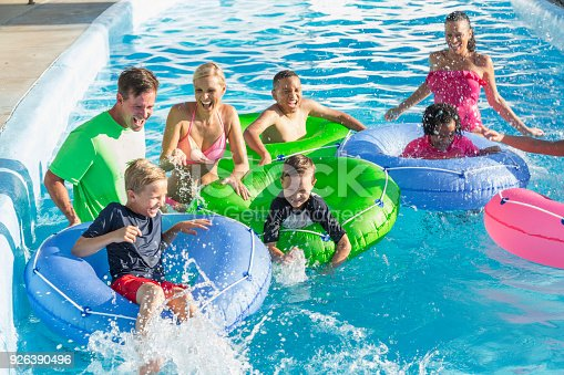 1091098220 istock photo Families and friends at water park on lazy river 926390496