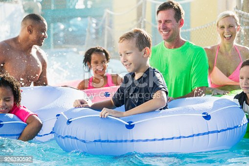 1091098220 istock photo Families and friends at water park on lazy river 926390592