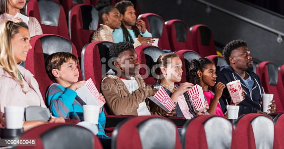 A multi-ethnic group of children with their parents watching a movie in a theater, eating popcorn. Two families are sitting in a row together. The boys are 11 and 13, and the girls are 10 and 12 years old. They have serious expressions on their faces.