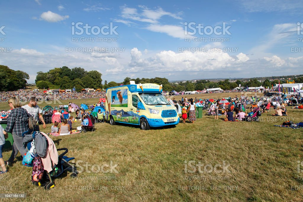 Families at an event sit in the sun next to an ice cream truck stock photo