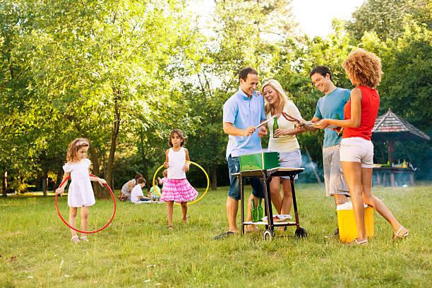 familien genießen sie ein barbecue. - kinder picknick spiele stock-fotos und bilder