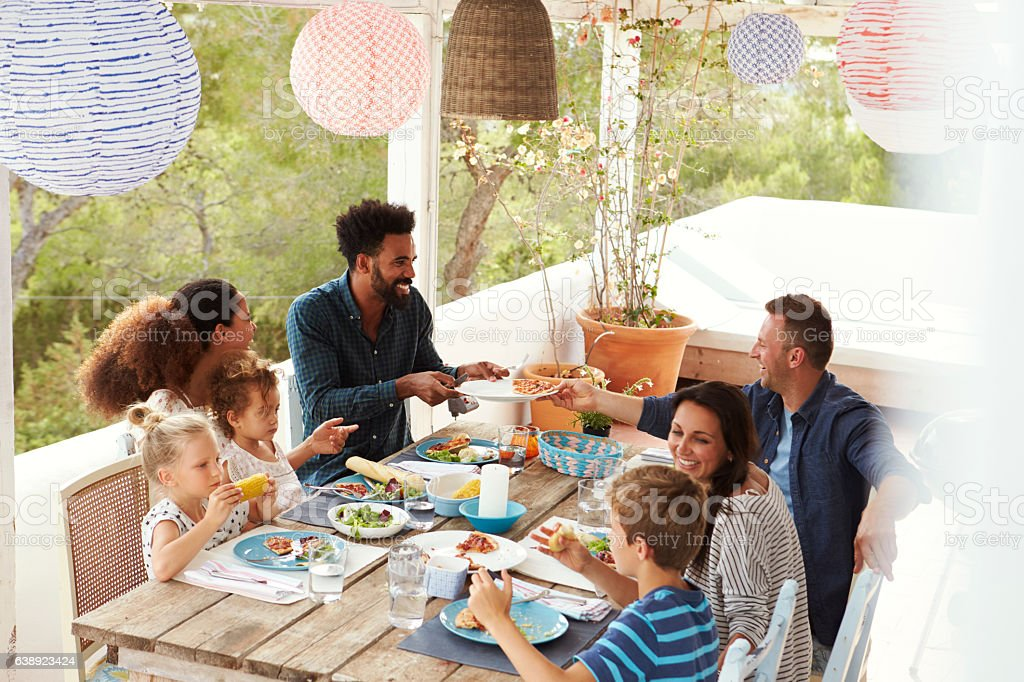 Families Enjoying Outdoor Meal On Terrace Together stock photo