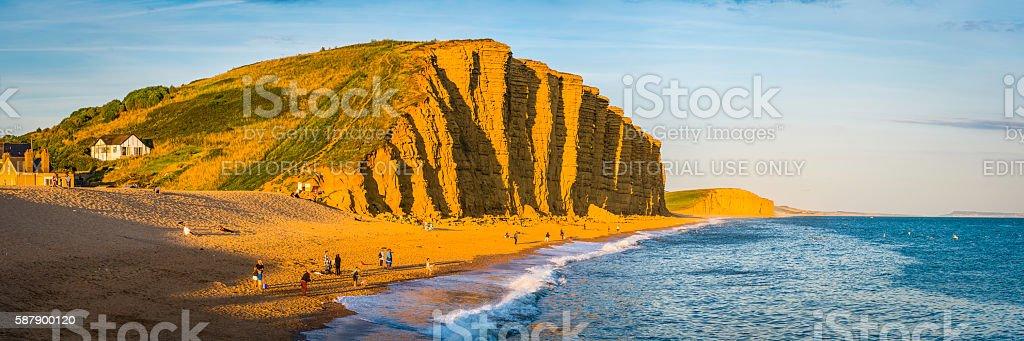Families fishermen on beach beneath golden cliffs West Bay Dorset stock photo