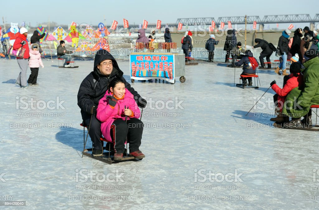 Families having fun riding rudimentary, rental sleds on frozen Songhua river. The river becomes a playfield during famous, annual Harbin Ice & Snow World Festival stock photo