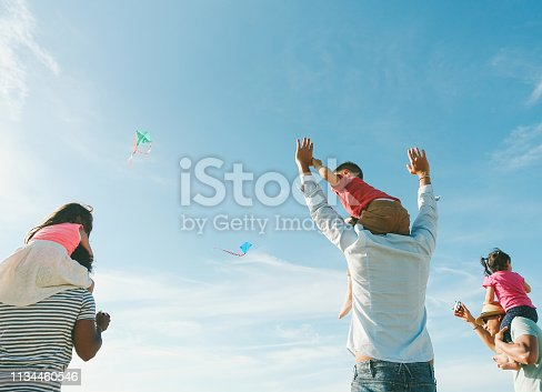 istock Families with children flying with kites on the beach at sunset - Adult friends playing with son and daughters on summer vacation - Holidays concept - Focus on left people - Retro filter 1134460546