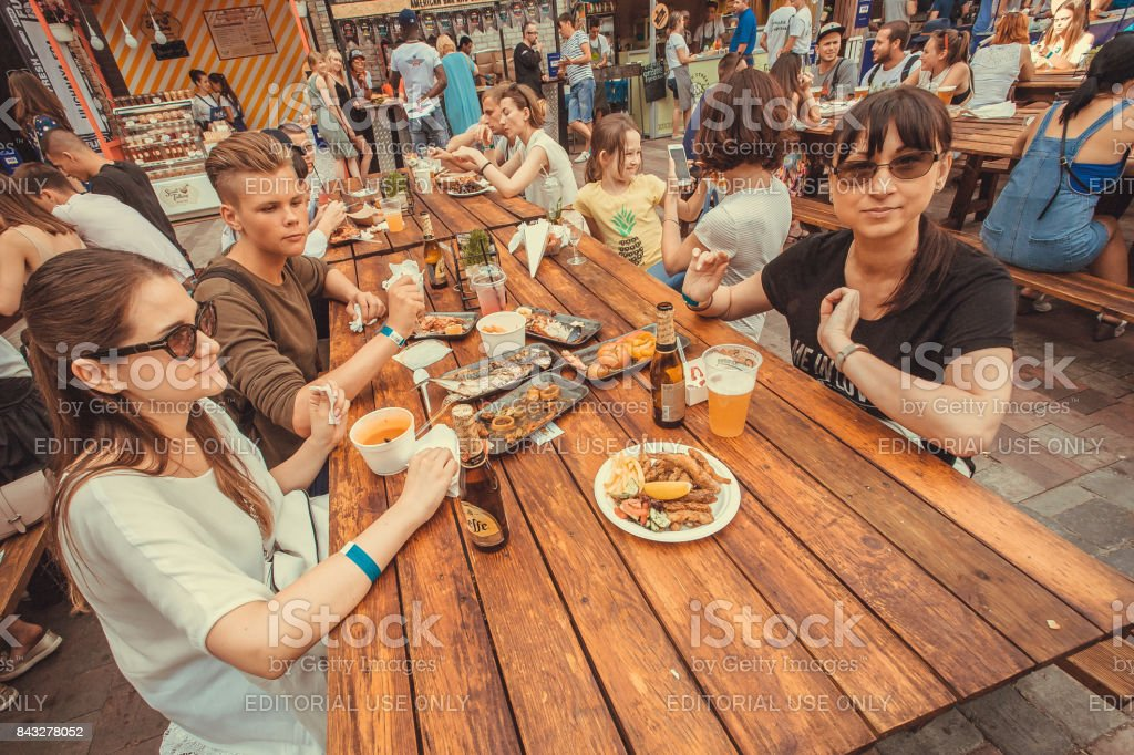 Families with teen children having dinner, eating and drinking during outdoor Street Food Festival - foto stock