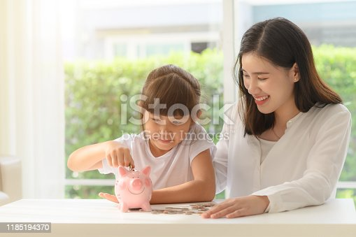 mother help daughter in saving money by collecting coils into piggy bank together