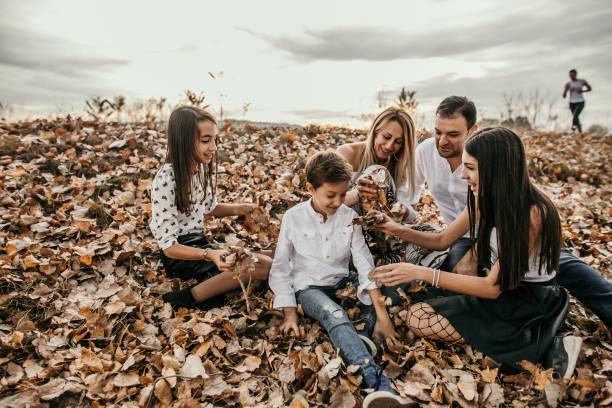 Aventura em família em folhas de Outono no parque - foto de acervo