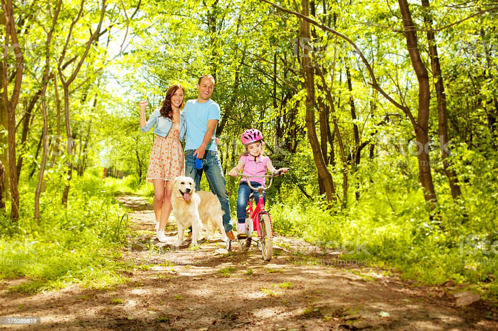 Family and dog enjoying a walk in the forest stock photo