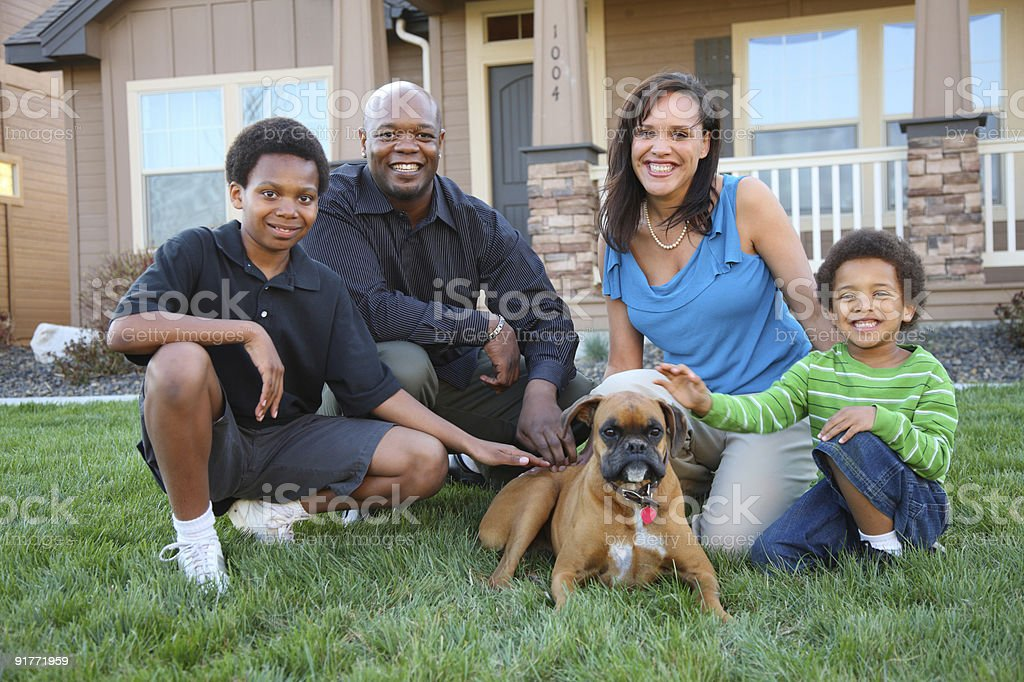 Family and dog in front of home stock photo
