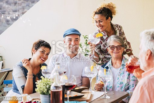istock Family and friends at lunch all together at home in the terrace - eating and drinking food and beverages - smile and having fun- friendship with mixed ages senior and middle age people 1133417004