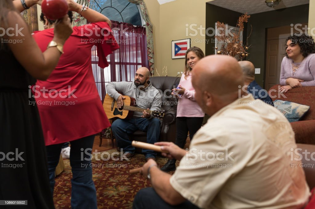 Family and friends dancing and playing musical instruments stock photo