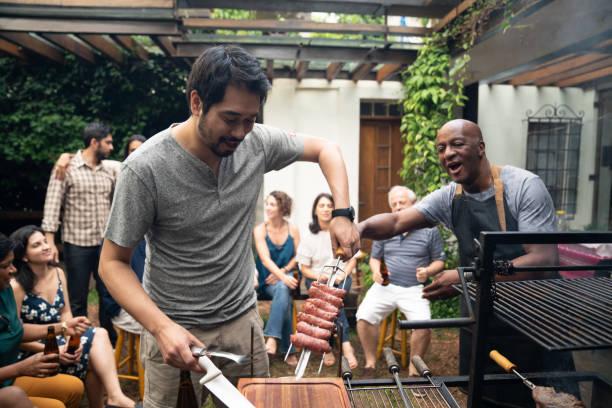 family and friends enjoying a barbecue party at home - vizinho imagens e fotografias de stock
