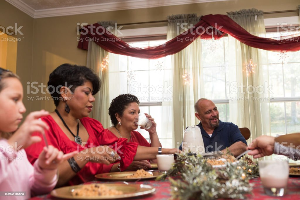 family and friends gather for Christmas celebration stock photo